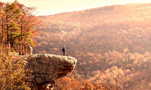 Man on a rock ledge along Hawksbill Crag in Arkansas