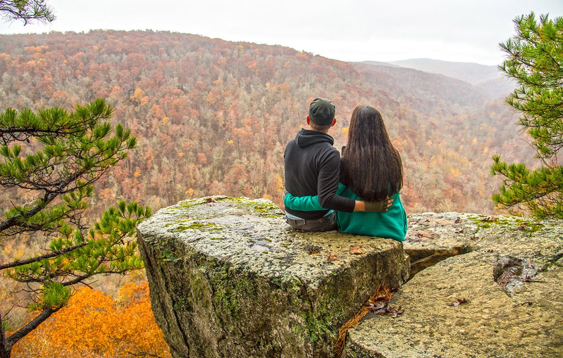 Couple taking in the scenic views along Hawksbill Crag trail in Arkansas