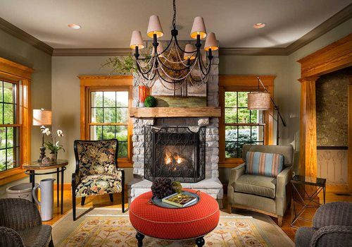 grand, ornate fireplace framed by open windows and plush chairs