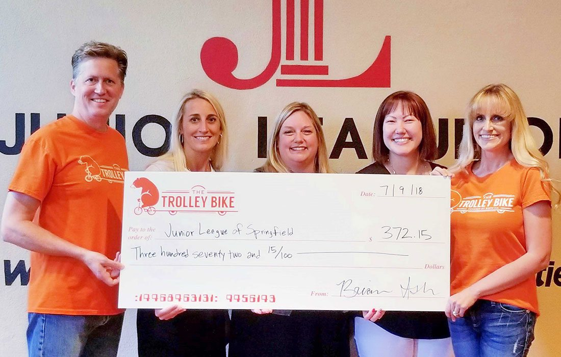 Brian Ash and Cortney Little-Ash (far right) present a check to Junior League of Springfield, MO