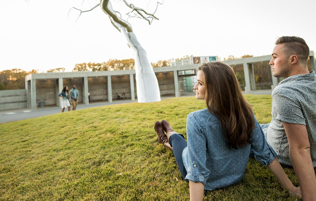 Couple sitting on the lawn outside Crystal Bridges in Bentonville AR
