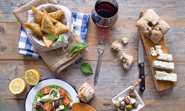 Greek food spread on a wooden tabletop.