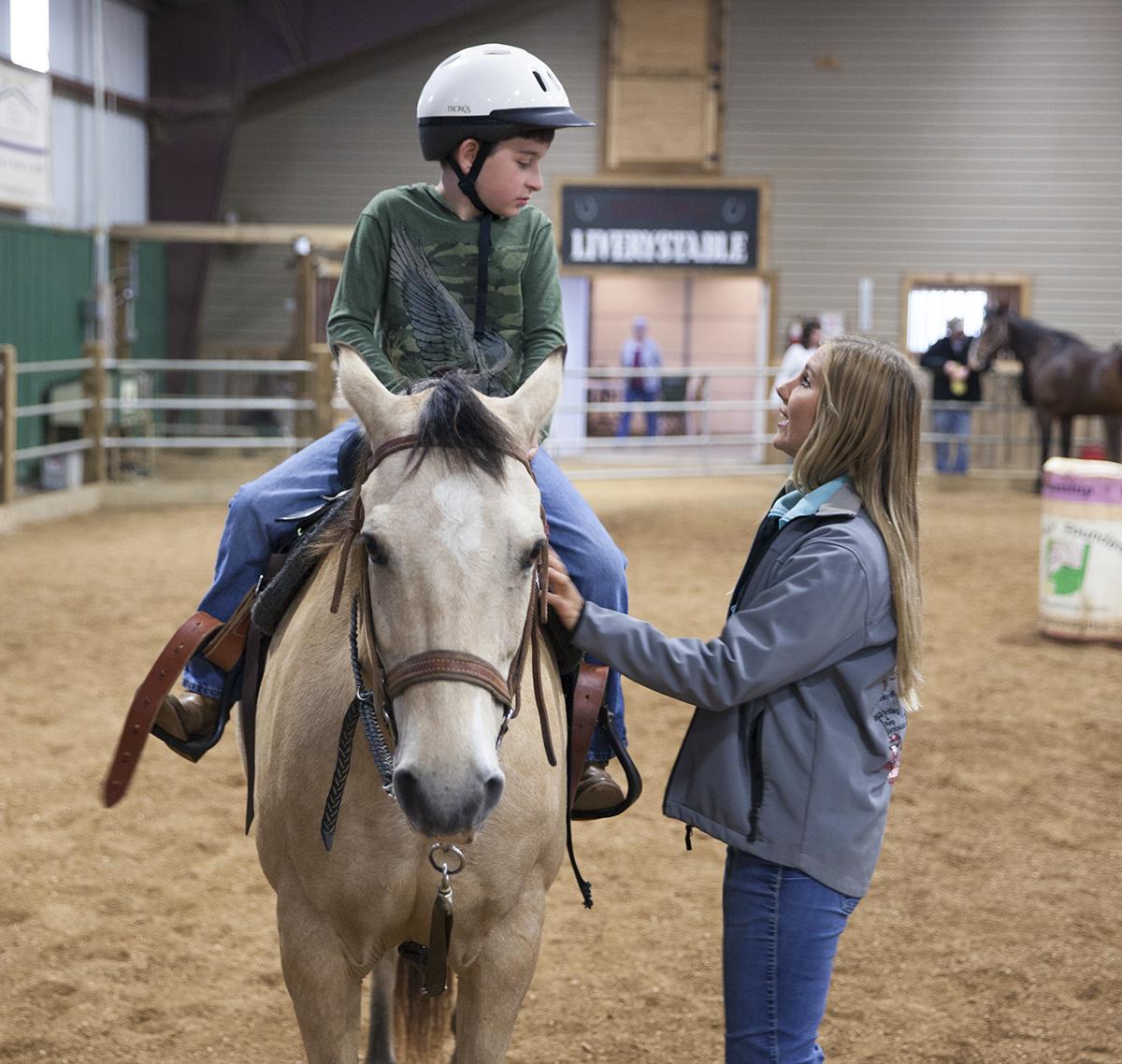 Senior arena instructor Loryn Barclay helps Karson Robb ride his horse.
