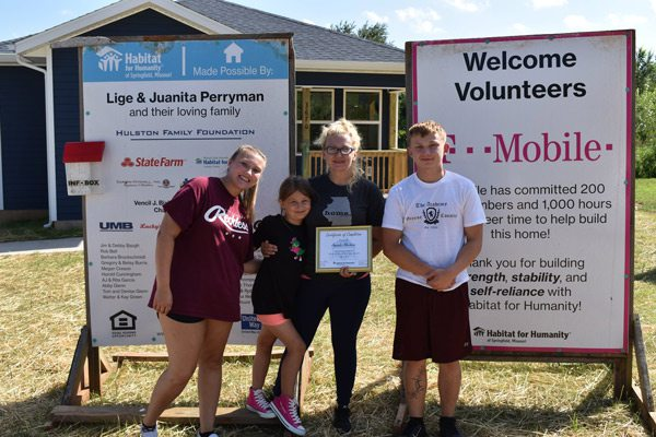 Family with Habitat for Humanity signs