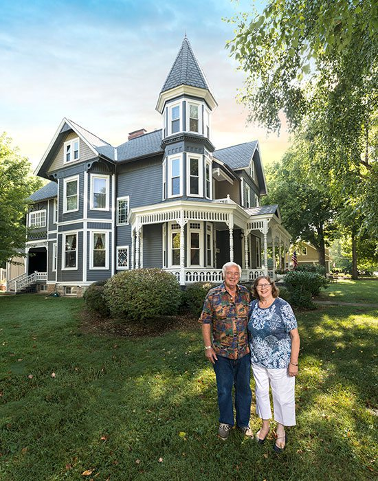 Wayne and Ellen Nielsen in front of their Queen-Anne style home