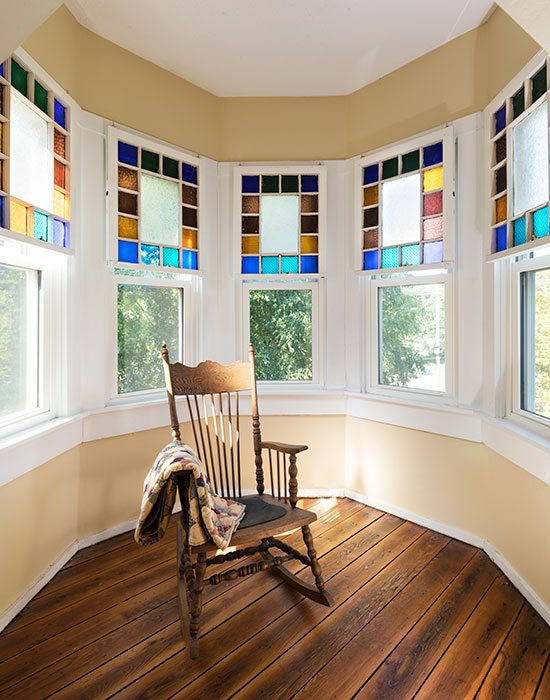 rocking chair and stained glass in turret of victorian home