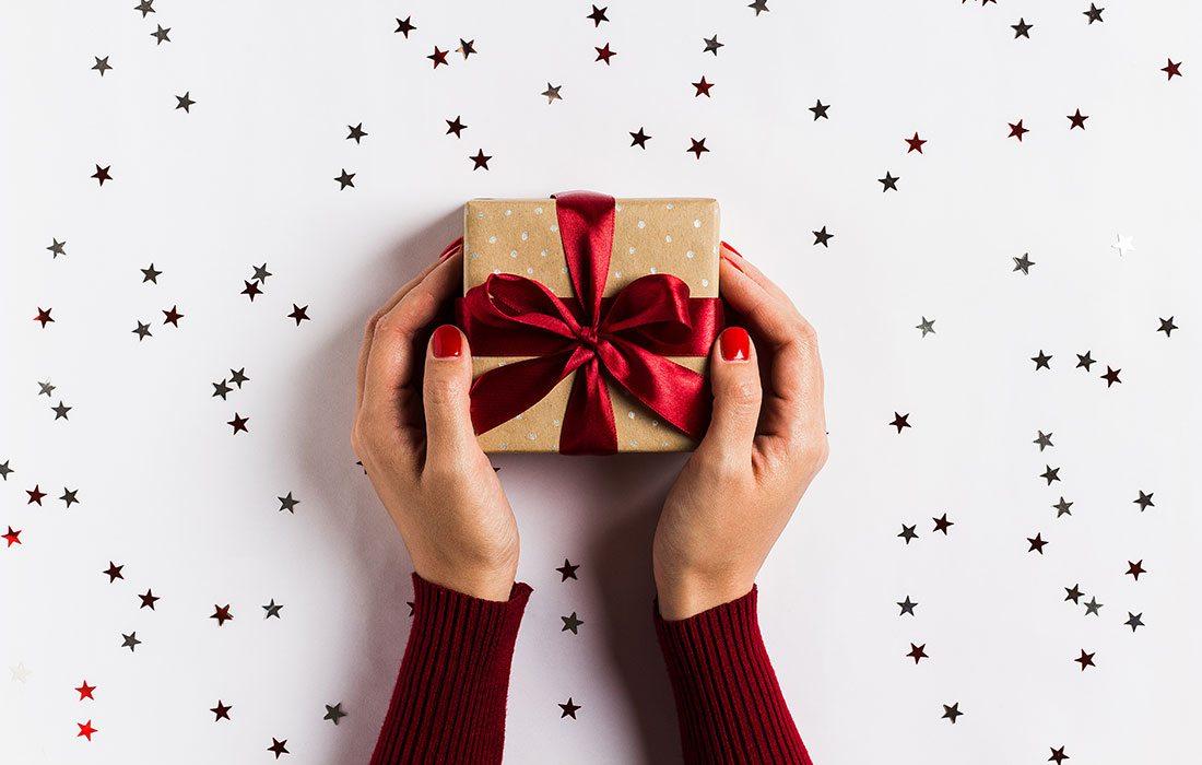 Woman's hands gifting a Christmas present