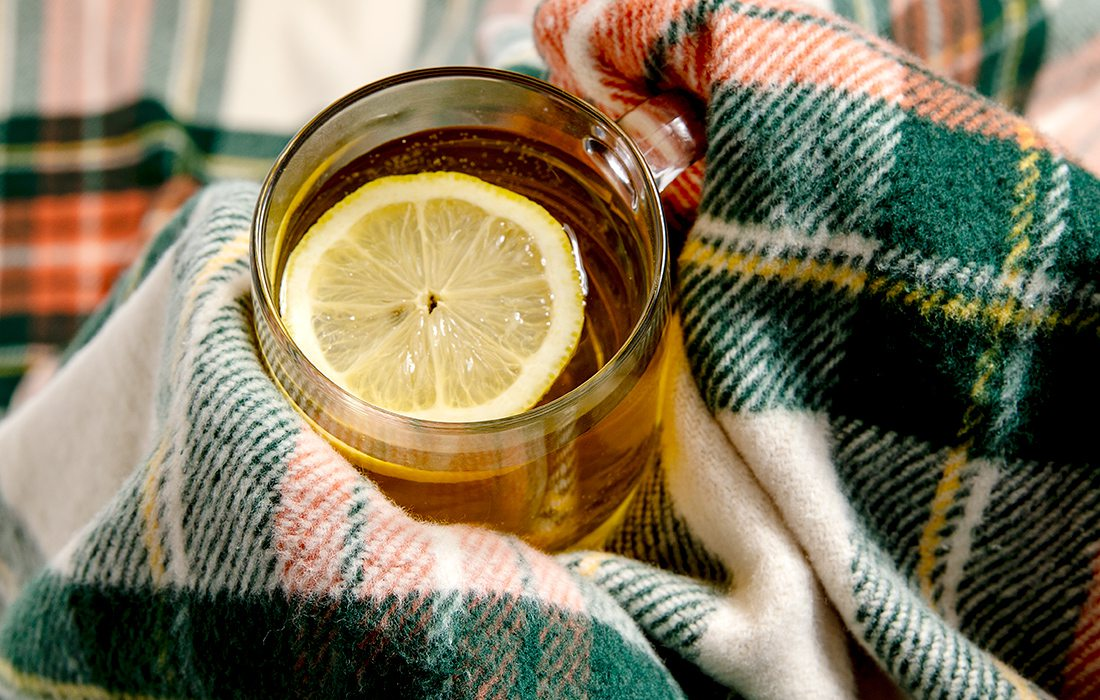 Hot toddy in a cozy plaid blanket
