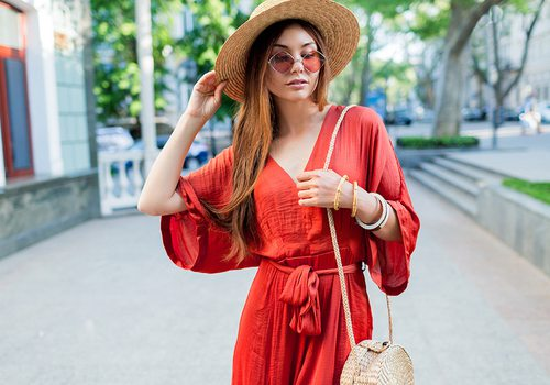 Young woman wearing a red jumpsuit and a straw hat