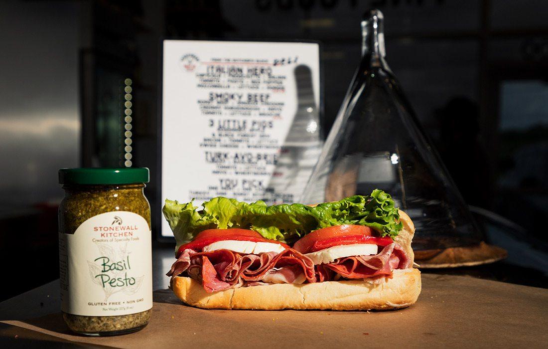 Sandwich next to basil pesto bottle