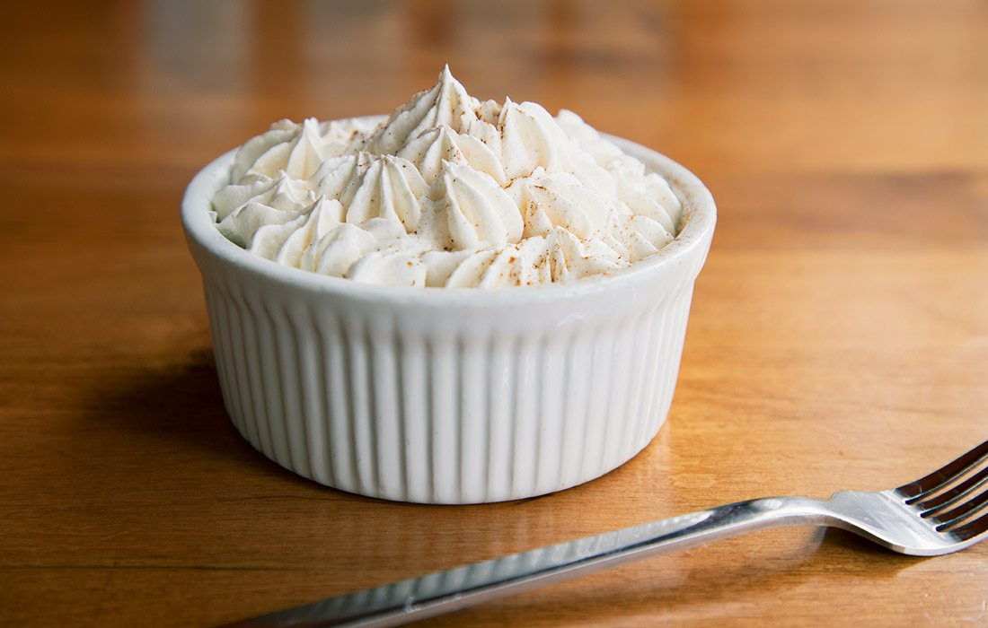 Coconut Tres Leches in white dish next to fork