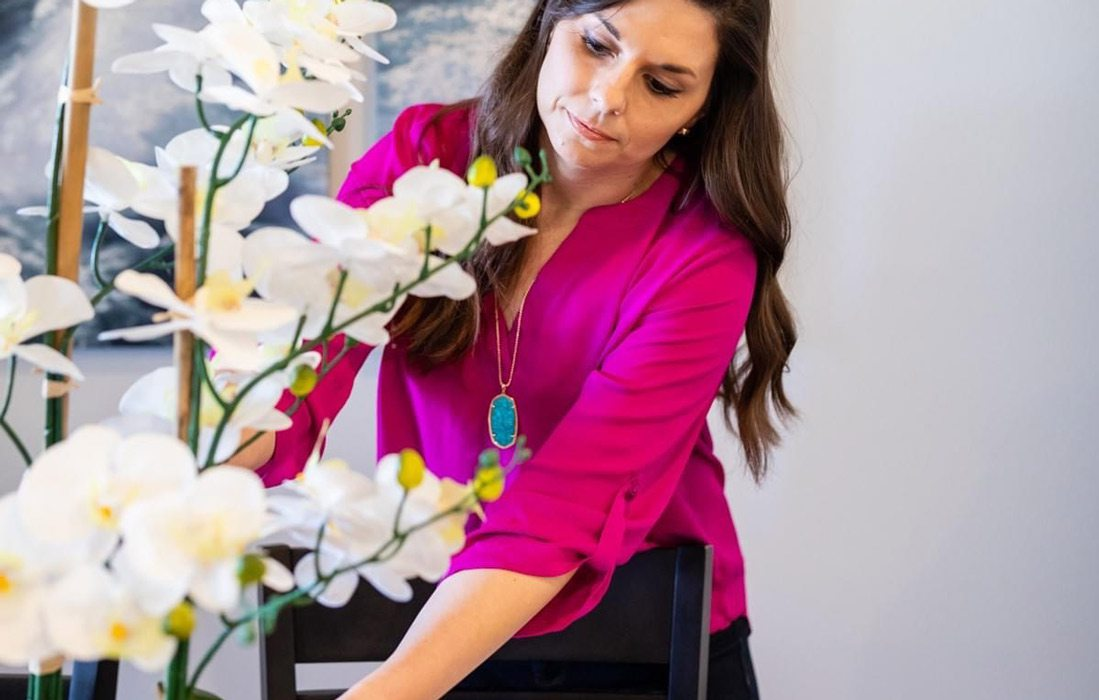 Woman stages vase of white flowers
