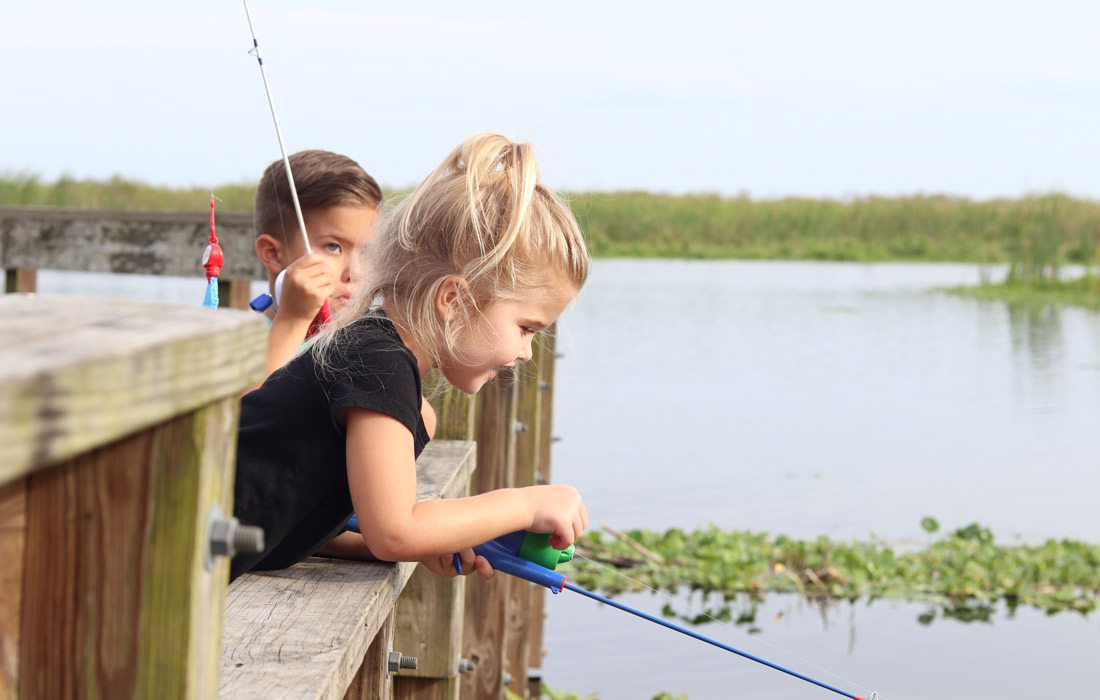 Two kids fishing off dock
