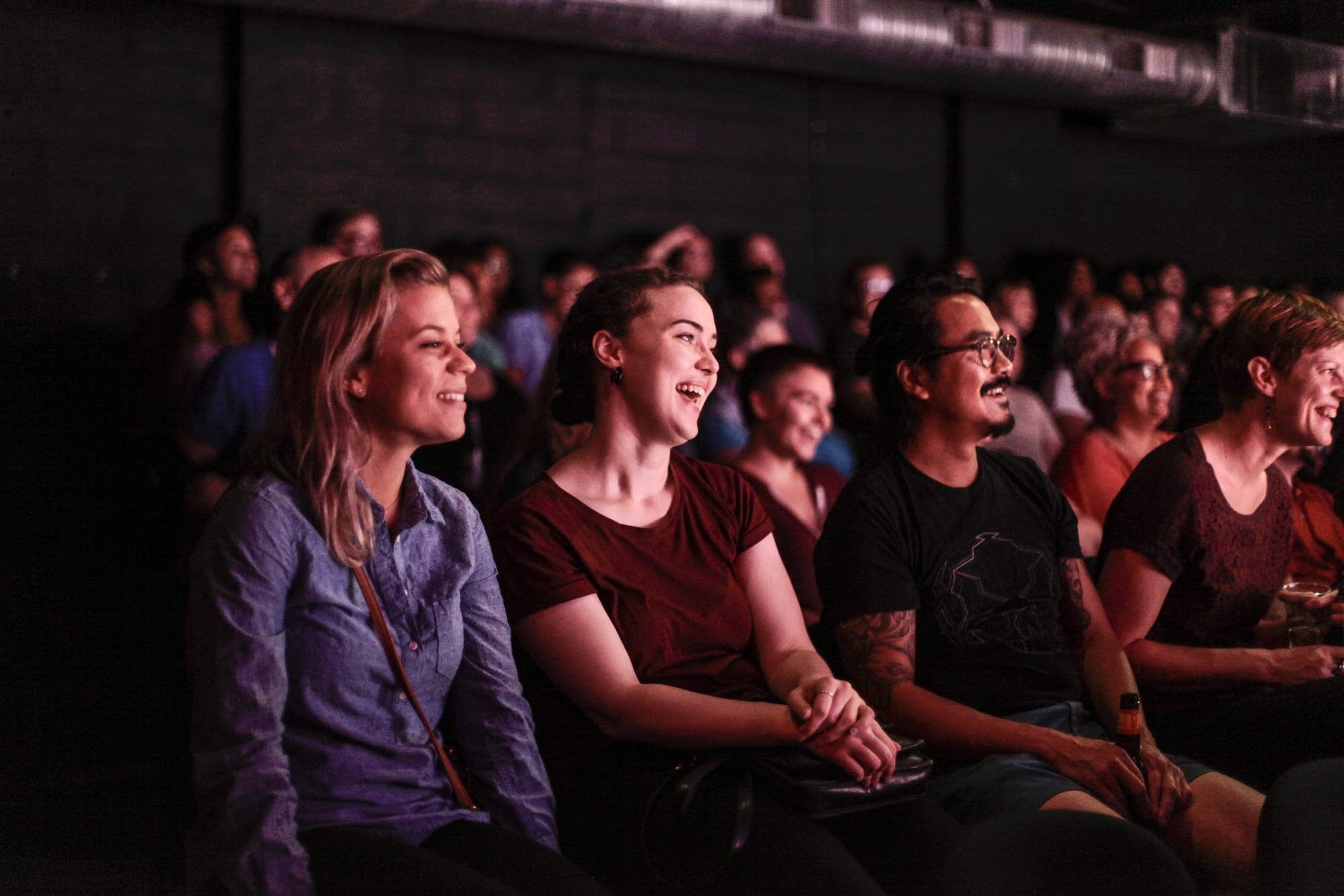 an audience laughing at a comedy show