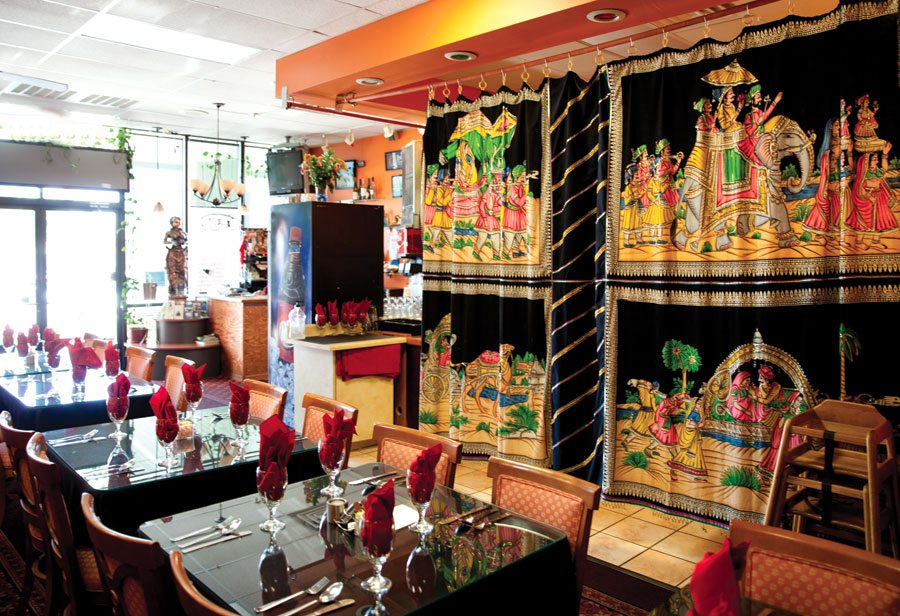 Indian restaurant with decorative curtains and table settings