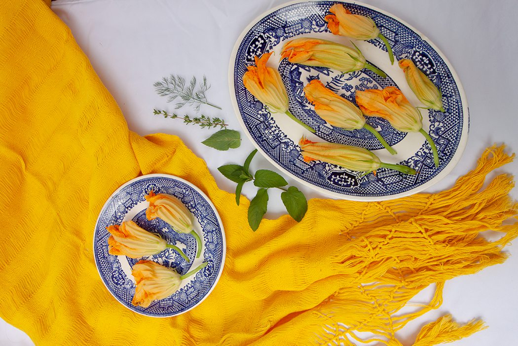 Squash blossoms laid out on blue china plates