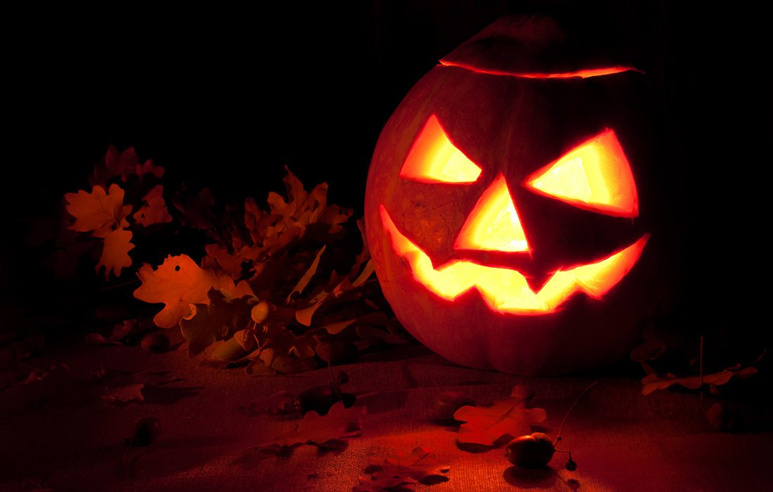 Jack O' Lantern with fallen leaves Shutterstock image.