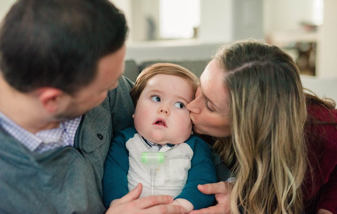 Parents hold baby and mom kisses babies cheek