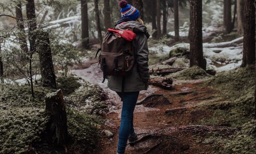Woman hiking in the woods during winter.