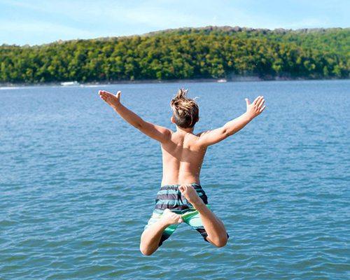 Boy jumping into lake