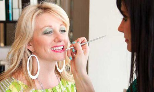 A woman puckers her lip while a stylist applies lip gloss