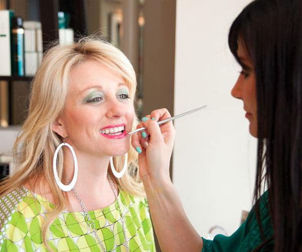 Beautiful blonde woman getting her makeup and lipstick done.