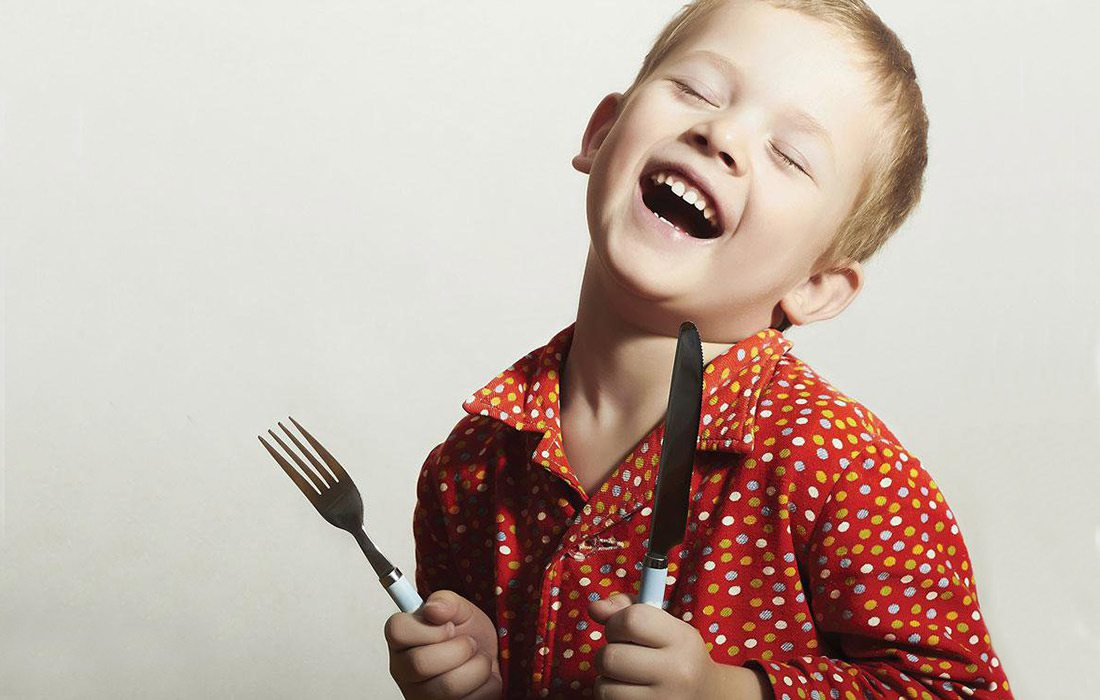 kid with a fork and a knife learning etiquette