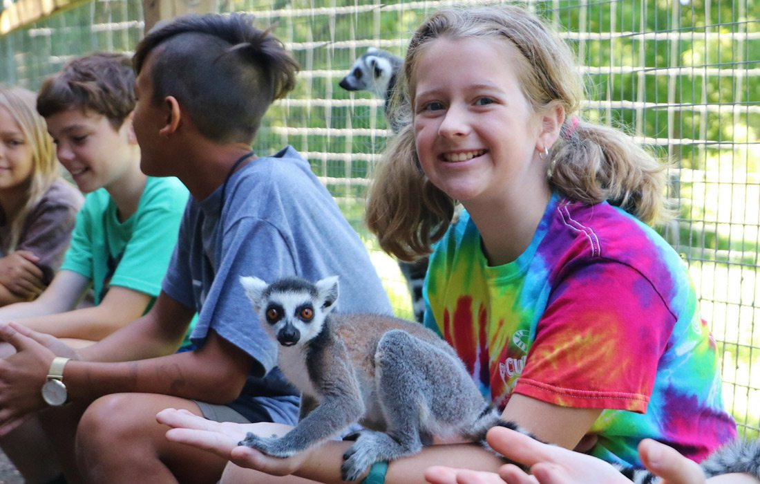 young girl at Cub Creek Science Camp with a Ringtail Lemur