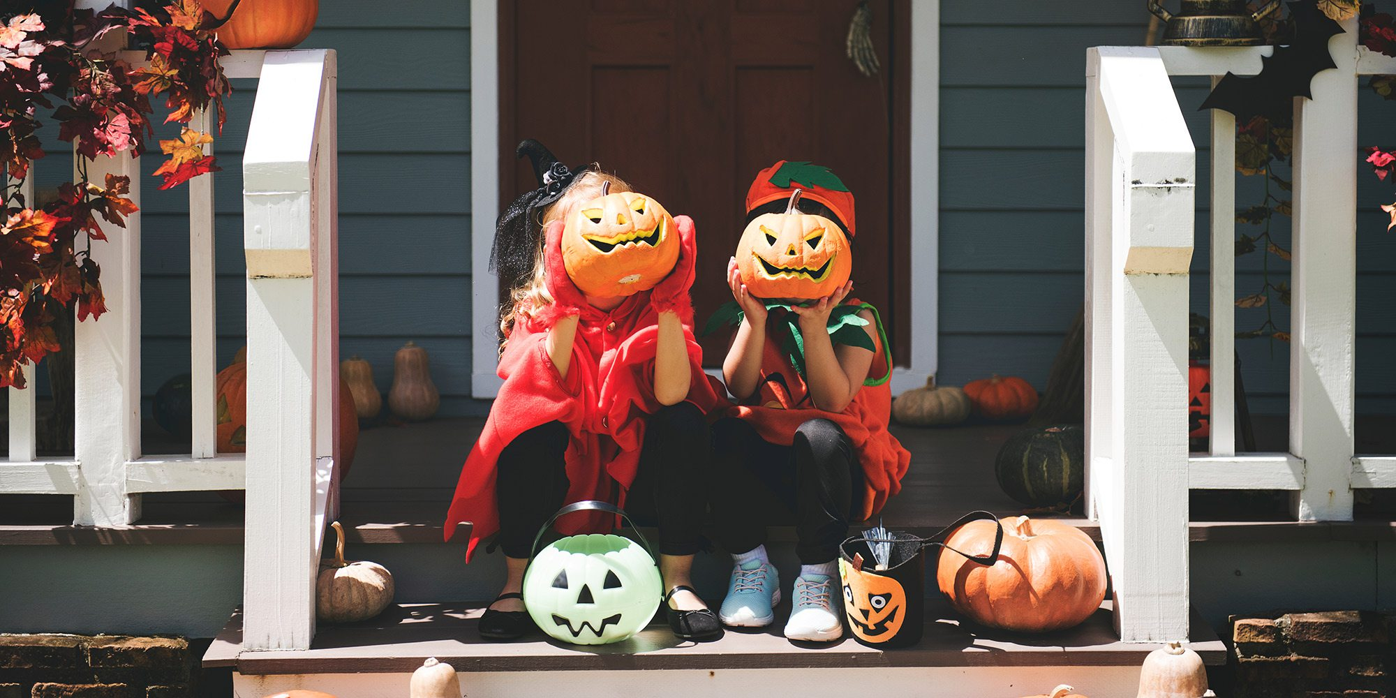 Two little kids in Halloween costumes showing off their carved pumpkins
