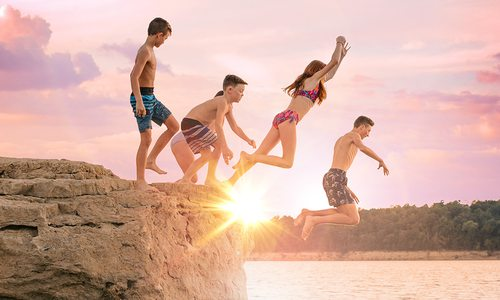 Family jumping off a bluff at Bull Shoals Lake at sunset