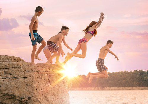 Family jumping off a bluff at Bull Shoals Lake at sunset