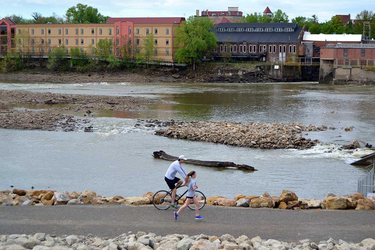 a woman runs and a man bikes along the river