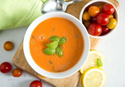 A bowl of gazpacho sits on a wooden slab with baby tomatoes and lemon slices surronding