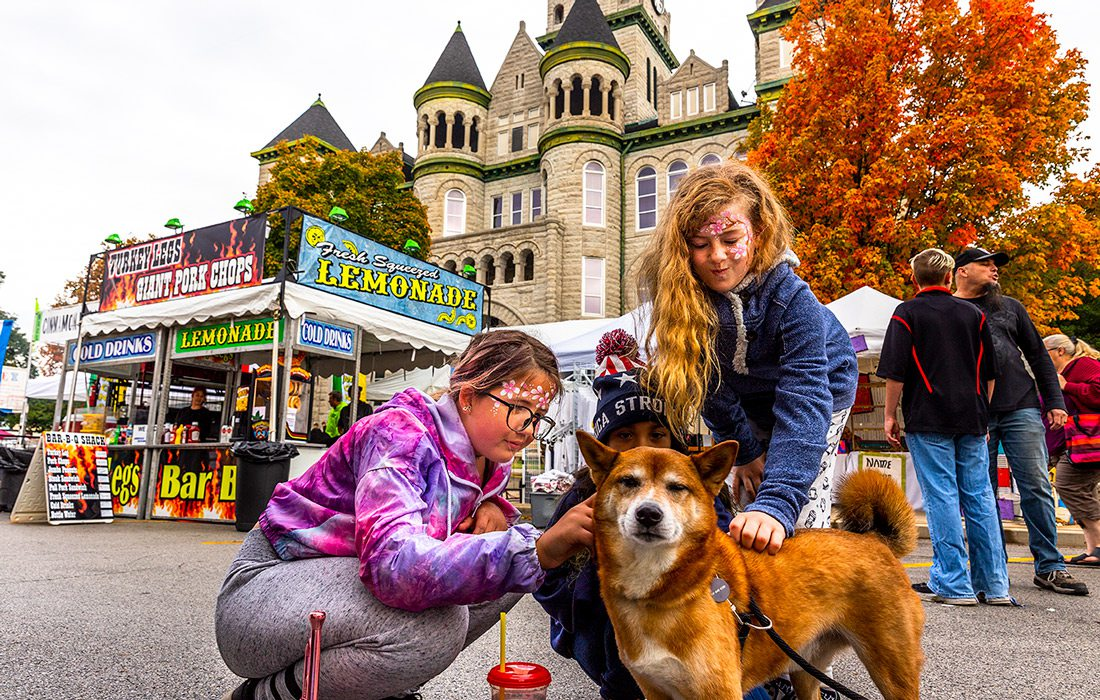 Two girls with a dog at the Maple Leaf Festival
