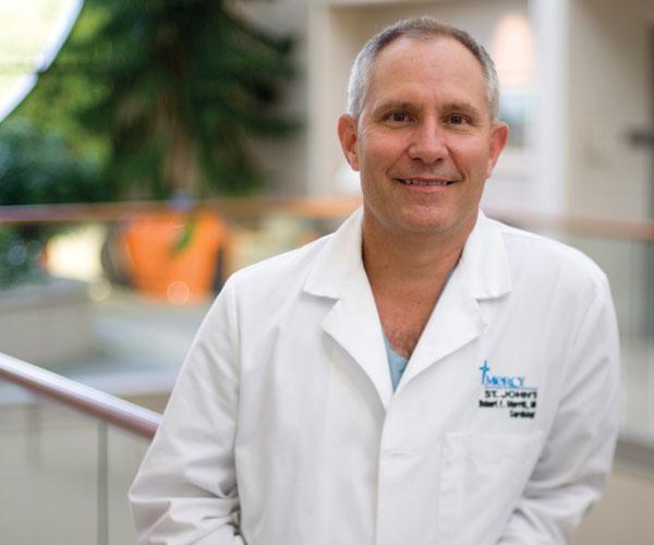 Doctor in white coat inside hospital lobby