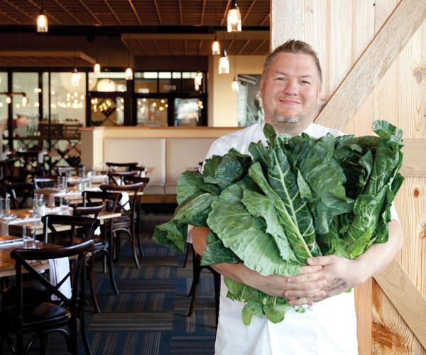 Chef holding greens inside farmhouse style restaurant