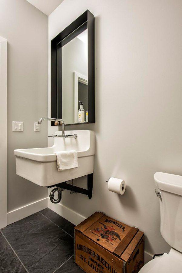 Minimalist bathroom with farmhouse sink by Jason Bekebrede.