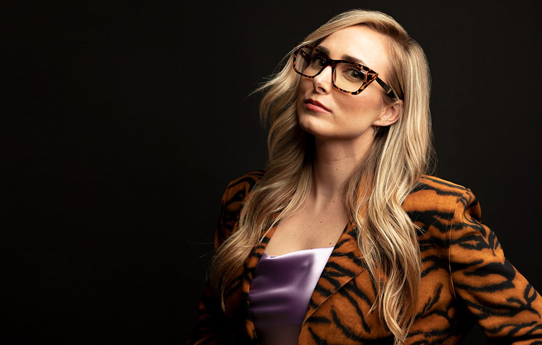 Woman wearing a tiger stripe jacket and tortious shell glasses