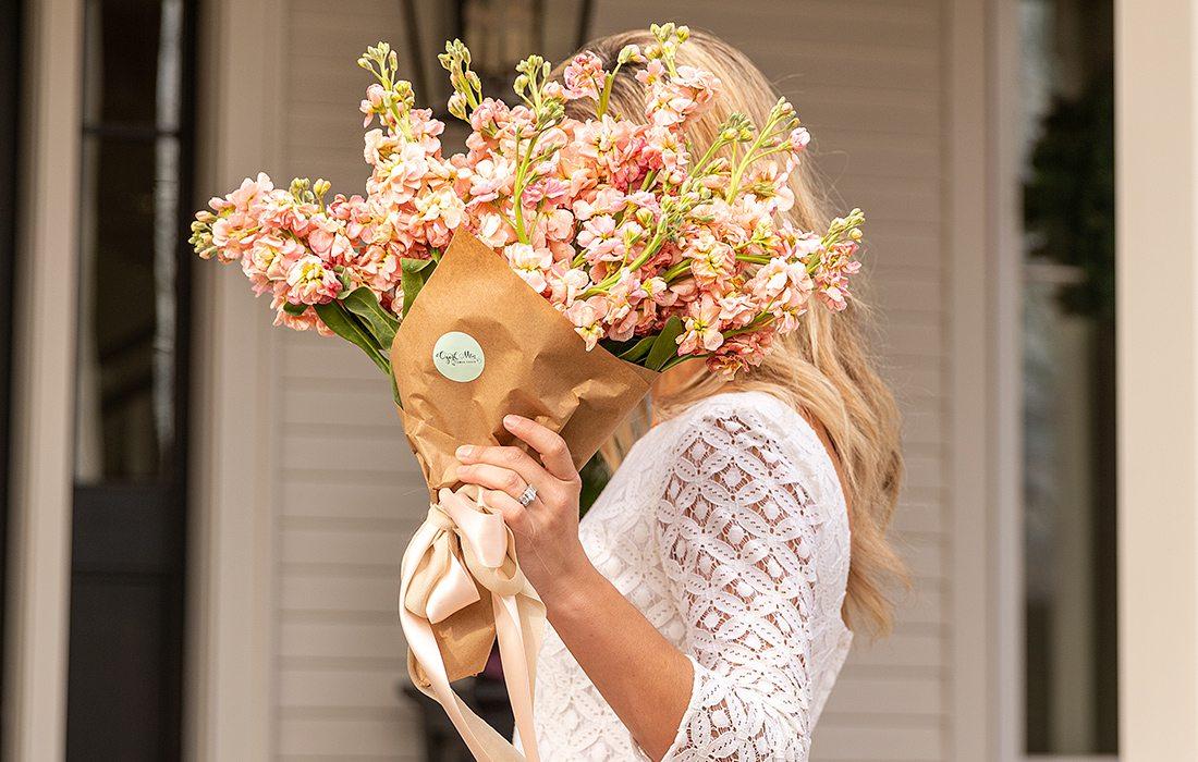 Jamie Stauffer holding a bouquet of flowers by Ozark Mtn Flower Truck in Springfield MO