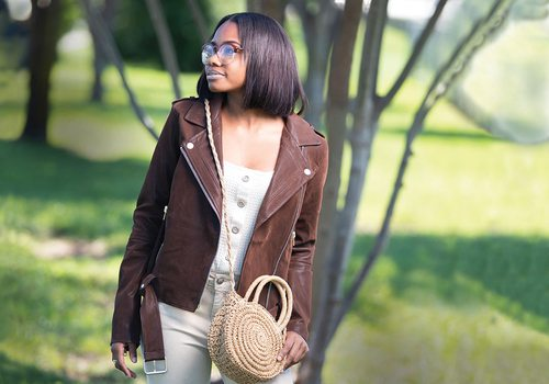 girl stands in brown jacket and tan purse in a park