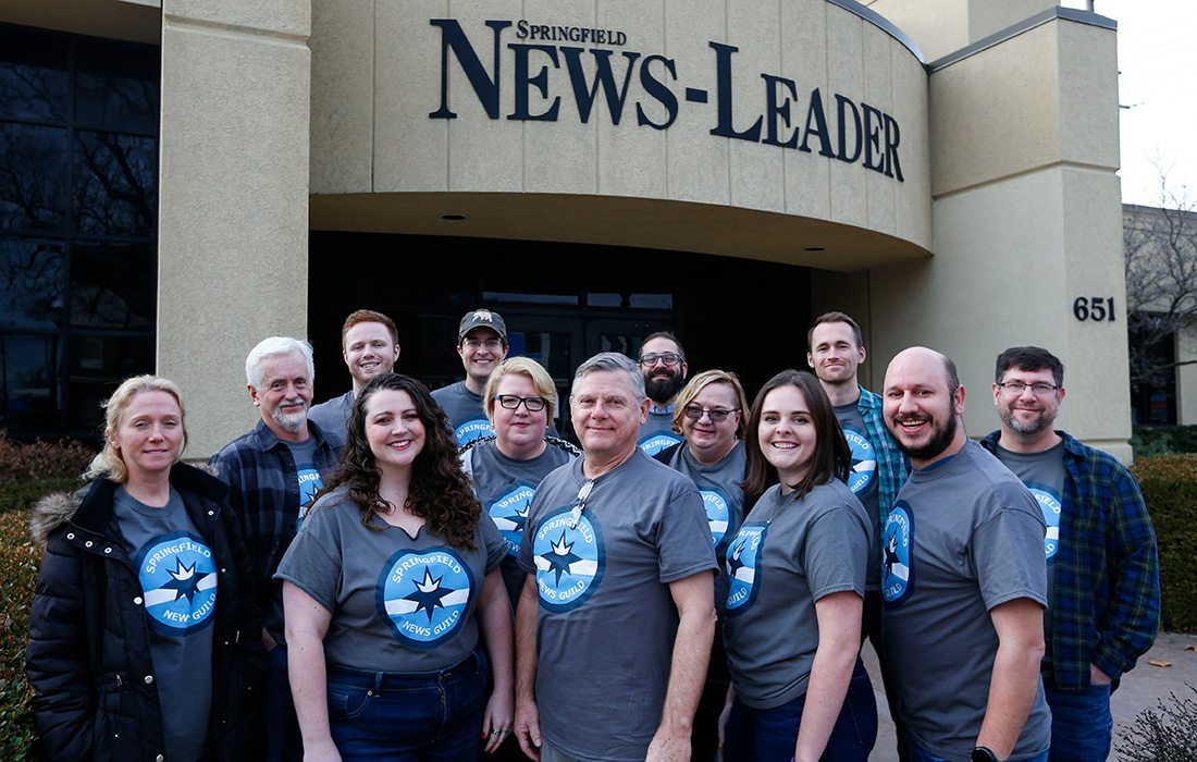 The news staff in front of their building