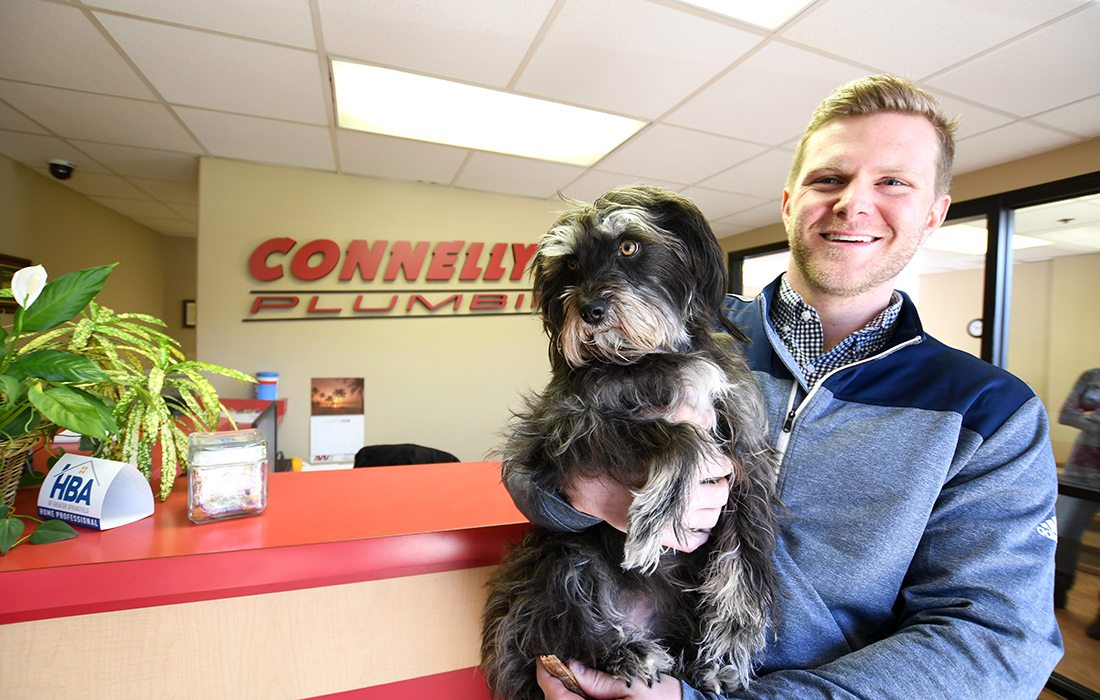 Lucy, a 4-year-old terrier mix and Brett Edwards at Connelly Plumbing, Heating & Air