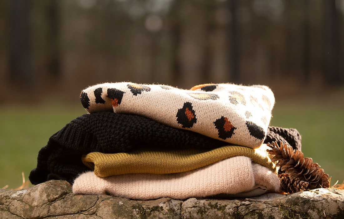 Sweaters piled on a log outdoors