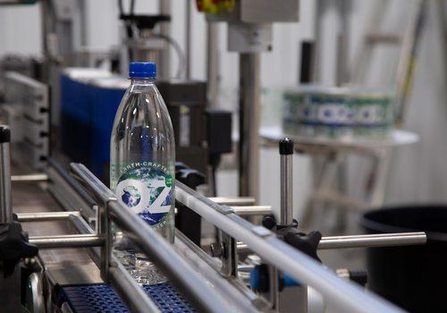 OzWater bottle on conveyor belt in Deer Lake Partners bottling plant.