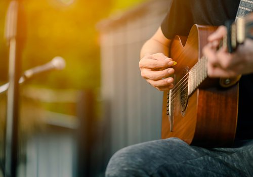 Closeup of someone playing an acoustic guitar outside