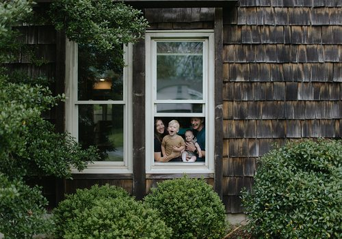 Olivia Jahnke and her family through a window at home