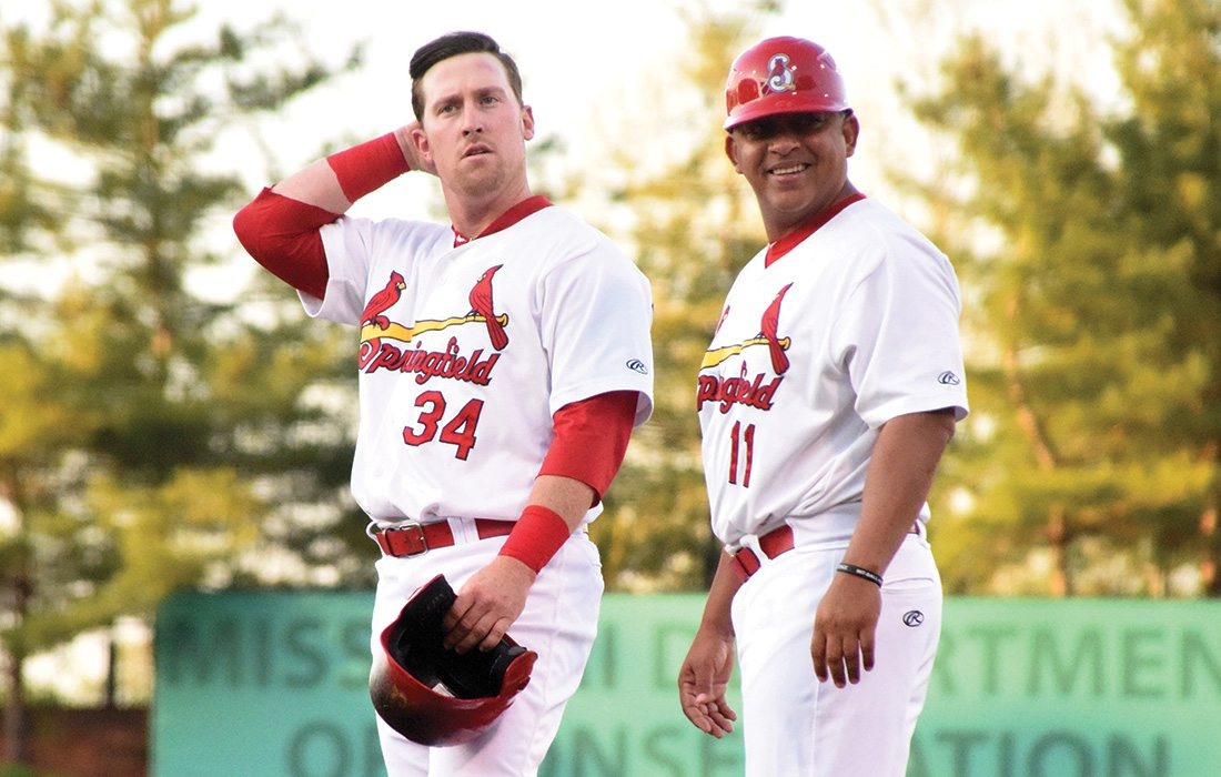 Coach Jobel Jimenez and John Nogowski stand of the field in their Cardinals uniform.