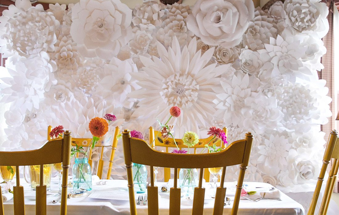 White flower arrangements over table and chairs.