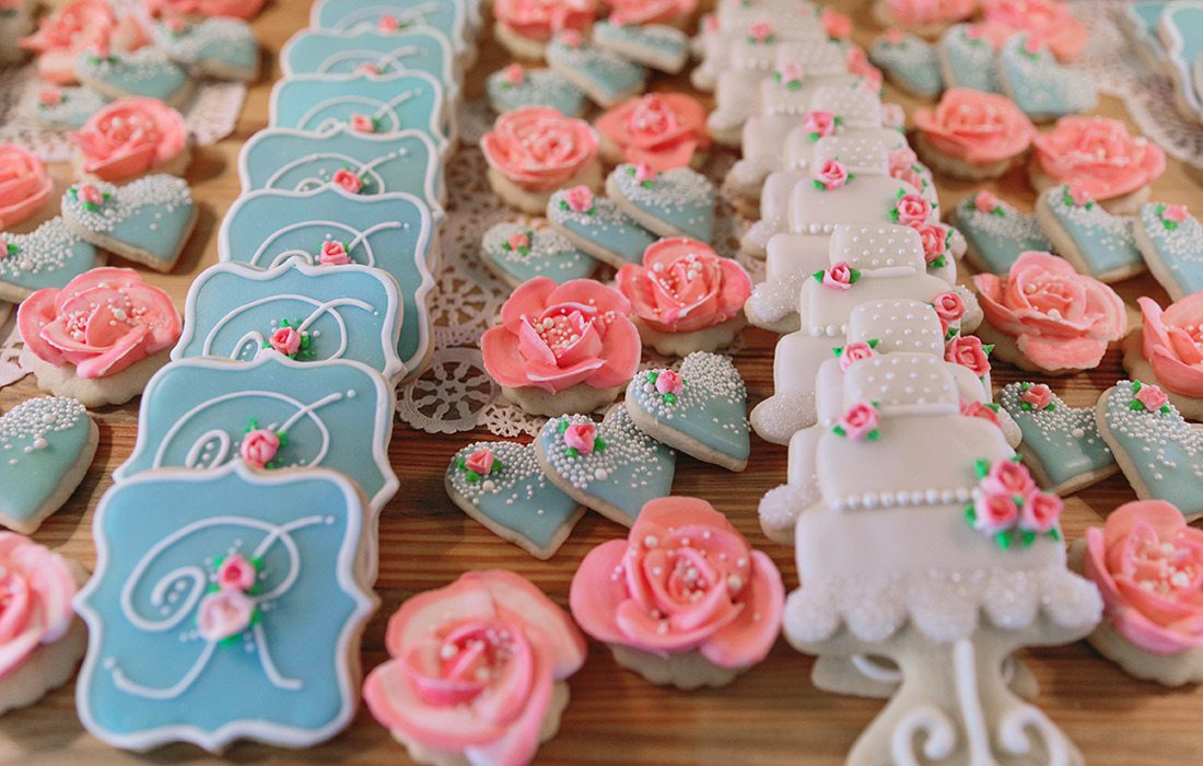 Different colored sugar cookies arranged in rows.