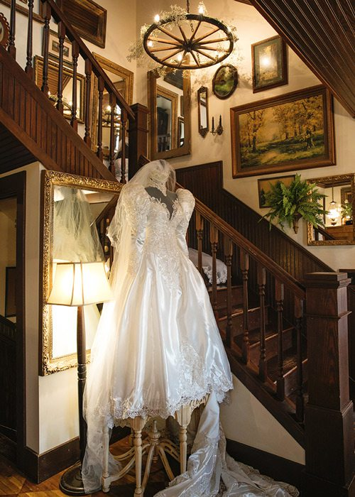 Wedding dress on display in front of staircase.